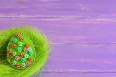 Ornamento do ovo da páscoa de feltro com flores plásticas Ovo de feltro no ninho e em placas de madeira roxas com lugar vazio par imagens de stock