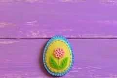 Ornamento do ovo da páscoa de feltro com o botão cor-de-rosa da flor em um fundo de madeira com espaço da cópia Ofícios da costur fotografia de stock royalty free