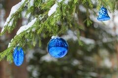 Ornamento efervescentes da prata e do ultramarine da quinquilharia do feriado do Natal fora em ramos nevado do abeto Imagem de Stock Royalty Free