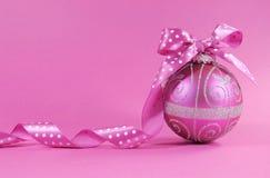 Ornamento festivo cor-de-rosa fúcsia bonito da quinquilharia com fita do às bolinhas em um fundo cor-de-rosa feminino com espaço  Fotografia de Stock Royalty Free