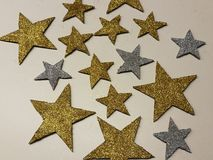 Ornamento a forma di stella brillante di Natale dell'argento dorato isolato su fondo bianco, sulla polvere di stella e sullo scin Immagine Stock