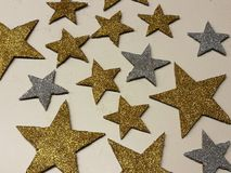 Ornamento a forma di stella brillante di Natale dell'argento dorato su fondo bianco, sulla polvere di stella e sullo scintillio d Immagini Stock