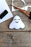 Ornamento lindo del fantasma de Halloween del fieltro, tijeras, hilo negro, pedazos y pedazos del fieltro en viejo fondo de mader Imagen de archivo