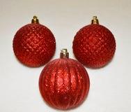 Ornamento luccicante rosso di Natale con un fondo vago Immagine Stock