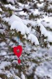 Ornamento nevoso de la Navidad del árbol de pino del corazón rojo Foto de archivo