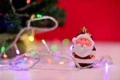 Ornamento Papá Noel enredado con las luces de la Navidad Imagen de archivo libre de regalías