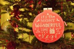 Ornamento rojo con la inscripción en el árbol de navidad fotos de archivo