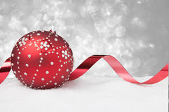 Ornamento rojo de la Navidad con la cinta en la nieve Fotos de archivo