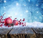 Ornamento rojo de la Navidad en la tabla Nevado con las nevadas en fondo fotos de archivo