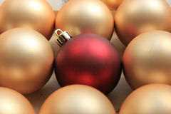 Ornamento rojo en una pila de ornamentos de oro Foto de archivo libre de regalías
