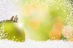 Ornamento verde di Natale su neve sopra un fondo astratto Fotografie Stock Libere da Diritti