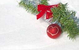 Ornamento vermelho brilhante da esfera do Natal na neve Fotografia de Stock
