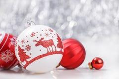Ornamentos blancos y rojos de la Navidad en fondo del bokeh del brillo con el espacio para el texto Navidad y Feliz Año Nuevo Foto de archivo libre de regalías