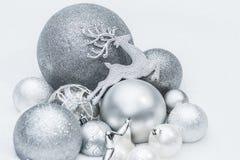 Ornamentos brillantes festivos de la Navidad del gris de plata con el reno de Papá Noel noveno en el fondo natural de la nieve Fotos de archivo