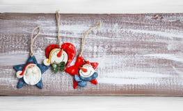 Ornamentos de cerámica de la Navidad con Papá Noel y muñeco de nieve en el CCB de madera Imagen de archivo libre de regalías