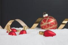 Ornamentos de la luz de la Navidad en la nieve Imagen de archivo