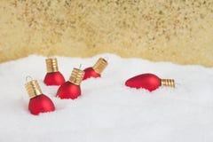 Ornamentos de la luz de la Navidad en la nieve con el fondo del oro Fotografía de archivo