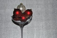 Ornamentos de la Navidad adentro sobre el vidrio clasificado del champán imagen de archivo