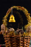 Ornamentos de la Navidad con la guirnalda de las gotas, de los conos del pino y de las bellotas poniendo en una cesta Imagen de archivo libre de regalías