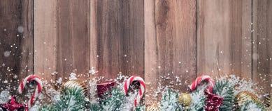 Ornamentos de la Navidad con nieve en el fondo de madera, diseño de la frontera Imagen de archivo libre de regalías