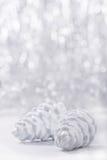 Ornamentos de la Navidad de plata y blanca en fondo del bokeh del brillo con el espacio para el texto Navidad y Feliz Año Nuevo Foto de archivo libre de regalías