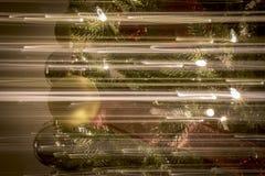 Ornamentos de la Navidad en las luces brillantes y felices de la noche con la cinta y el brillo Imagen de archivo libre de regalías
