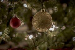Ornamentos de la Navidad en las luces brillantes y felices de la noche con la cinta y el brillo Foto de archivo