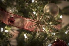 Ornamentos de la Navidad en las luces brillantes y felices de la noche con la cinta y el brillo Imágenes de archivo libres de regalías