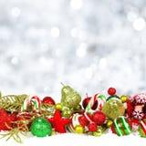 Ornamentos de la Navidad en nieve con el fondo del centelleo Fotografía de archivo libre de regalías