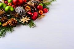 Ornamentos de la Navidad, ramas del abeto y conos rojos y verdes del pino Foto de archivo libre de regalías