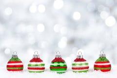 Ornamentos de la Navidad roja, verde, blanca en nieve con el fondo del centelleo Imágenes de archivo libres de regalías