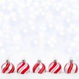 Ornamentos de la Navidad roja y blanca en nieve con el fondo del centelleo Imagen de archivo