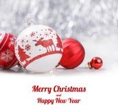 Ornamentos de la Navidad y rama de árbol blancos y rojos de abeto en fondo del bokeh del brillo con el espacio para el texto Navi Fotos de archivo