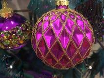 Ornamentos de las chucherías del árbol de navidad del oro y del fucsia Imágenes de archivo libres de regalías
