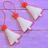 Ornamentos de los árboles de navidad en un fondo de madera púrpura Ornamentos hechos a mano del fieltro Proyectos de costura de l Foto de archivo libre de regalías