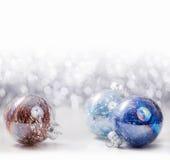 Ornamentos de plata y azules de la Navidad en fondo del bokeh del brillo con el espacio para el texto Navidad y Feliz Año Nuevo Imagen de archivo