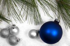 Ornamentos de plata y azules de la Navidad en nieve Foto de archivo