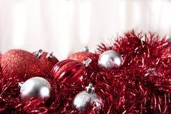 Ornamentos de plata y rojos de la Navidad en la guirnalda Fotografía de archivo