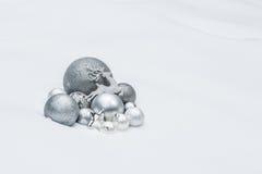 Ornamentos decorativos grises metálicos de la Navidad con el reno de Papá Noel en el fondo natural de la nieve Imagenes de archivo