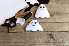 Ornamentos hechos a mano de los fantasmas de Halloween Dos pequeños fantasmas del fieltro, pedazos del fieltro, tijeras, hilo, ag Fotos de archivo
