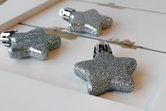 Ornamentos relucientes de la estrella en la madera blanca Imágenes de archivo libres de regalías