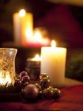 Ornamentos rojos de la bola de la Navidad con las velas ardientes Foto de archivo libre de regalías