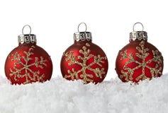 Ornamentos rojos de la Navidad con los copos de nieve en nieve Foto de archivo libre de regalías
