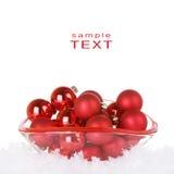 Ornamentos rojos de la Navidad en el tazón de fuente de cristal con nieve Imagen de archivo