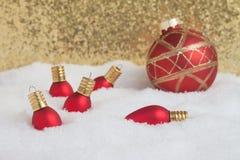 Ornamentos rojos de la Navidad en la nieve con el fondo del oro Foto de archivo