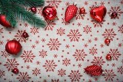 Ornamentos rojos de la Navidad y árbol de Navidad en fondo de la lona con los copos de nieve rojos del brillo Tarjeta de Navidad  Imagen de archivo
