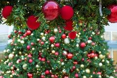 Ornamentos rojos del día de fiesta de la Navidad en el primer de la guirnalda Imagenes de archivo