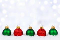 Ornamentos rojos y verdes de la Navidad en nieve con el fondo del centelleo Imagen de archivo