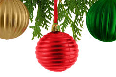 Ornaments. Gold,red and green ornaments hanging from branch of evergreen, isolated on white stock image