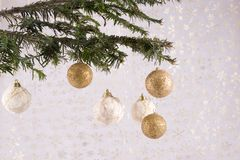 Ornaments on Christmas tree. Silver and gold ornaments hanging from branch of Christmas tree Royalty Free Stock Image